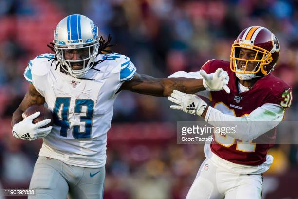 Bo Scarbrough of the Detroit Lions carries the ball and attempts to fight off a tackle of Fabian Moreau of the Washington Redskins during the second...