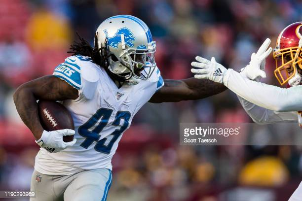 Bo Scarbrough of the Detroit Lions carries the ball and attempts to stiff-arm Fabian Moreau of the Washington Redskins during the second half at...