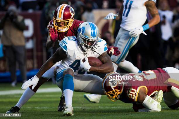 Bo Scarbrough of the Detroit Lions is tackled by Landon Collins and Quinton Dunbar of the Washington Redskins during the second half at FedExField on...
