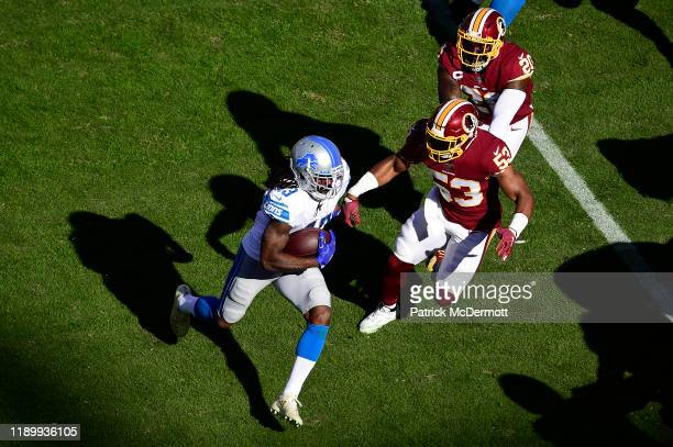 Bo Scarbrough of the Detroit Lions runs with the ball against Jon Bostic of the Washington Redskins in the first half at FedExField on November 24...