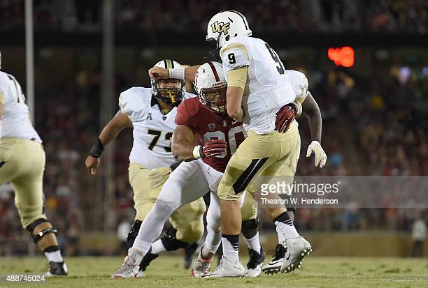Bo Schneider of the UCF Knights just gets his pass off before getting hit by Solomon Thomas of the Stanford Cardinal in the second quarter during an...