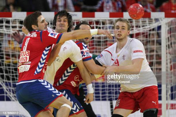 Bo Spellenberg of Denmark and Rene Toft Hansen dden0 defend against Nikola Manojlovic of Serbia during the Men's European Handball Championship final...