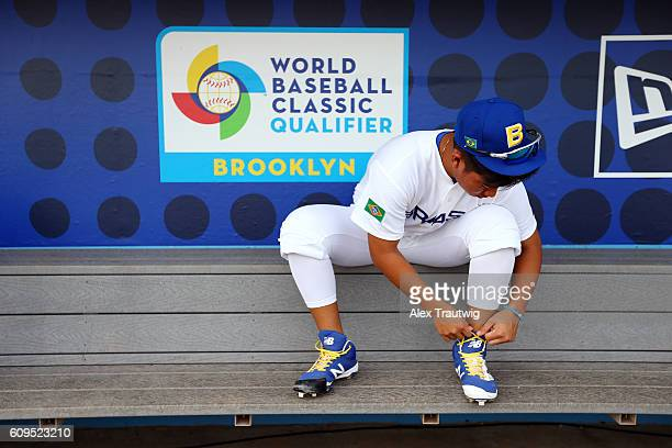 Bo Takahashi of Team Brazil ties his cleats in the dugout during workouts at MCU Park prior to the start of the 2016 World Baseball Classic Qualifier...