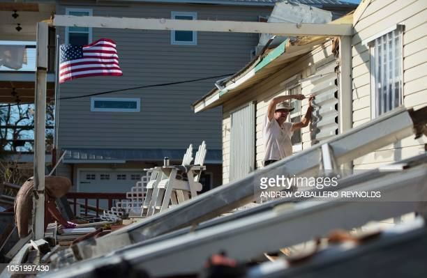 Bo Williams Glenn takes protective siding off his house on Port St Joe beach Florida on October 12 two days after hurricane Michael hit the area...