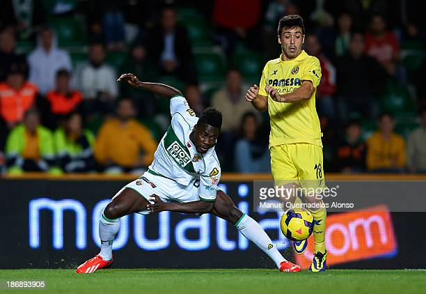 Boakye of Elche competes for the ball with Jaume Costa of Villarreal during the La Liga match between Elche CF and Villarreal CF at Estadio Manuel...