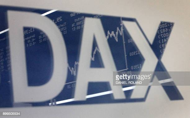 A board displaying the chart of German share index DAX reflects in a logo of the DAX at the stock exchange in Frankfurt am Main western Germany on...