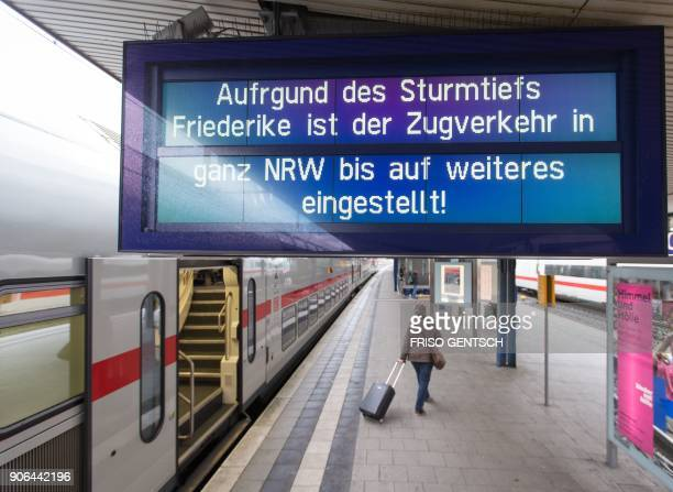 A board displays the cancellation of rail traffic due to bad weather conditions across the western state of North RhineWestphalia on a platform at...