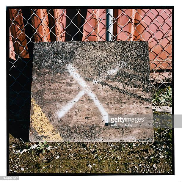 Board Leaning on Chain Link Fence