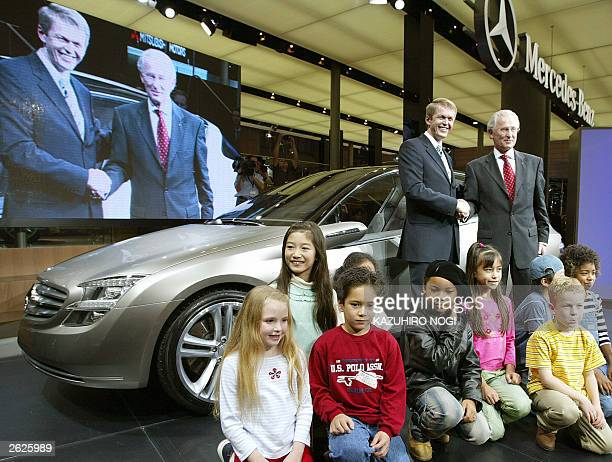 Board members of Daimler Chrysler AG Jurgen Hubbert and Thomas Weber shake hands in front of its newly unveiled research vehicle 'F 500 Mind' during...