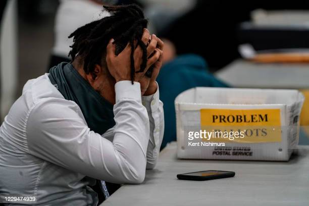 Board of elections worker takes a quick break after processing ballots at the Detroit Department of Elections Central Counting Board of Voting...