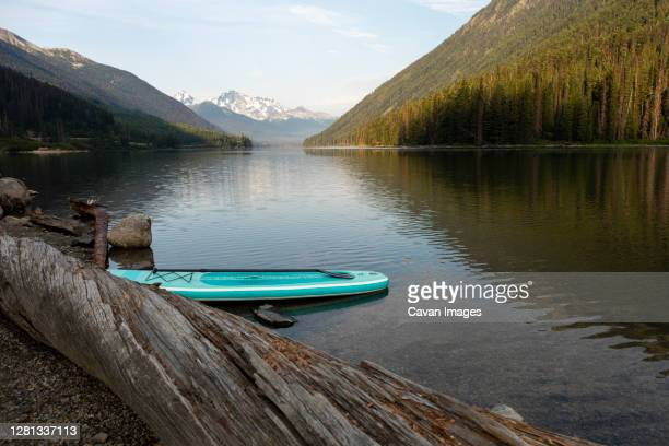 sup board on shore of lake on background of mountain ridge in morning - seeufer stock-fotos und bilder