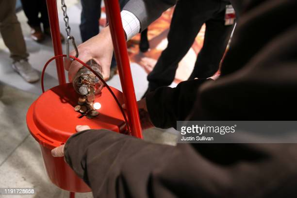 Board President Bevan Dufty pours change into a Salvation Army red kettle at the Powell Street Bay Area Rapid Transit station on December 03 2019 in...