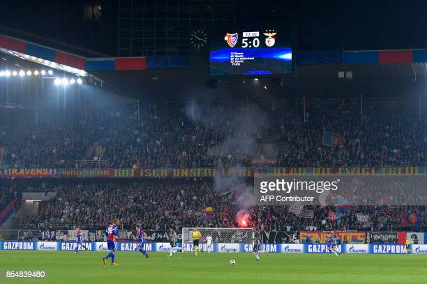 A board shows the final score as a flare is lit in the stands during the UEFA Champions League Group A football match between FC Basel 1893 and...