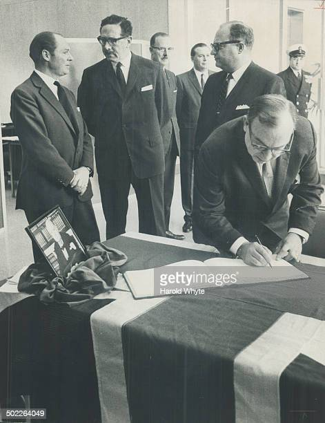 Board signs churchill book Controller Herbert Orliffe signs book of condolence which was opened at the British Government Office on Univesity Ave...