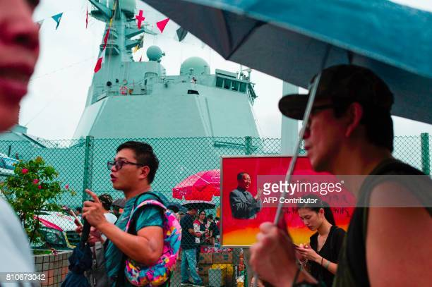 A board with a portrait of Mao Zedong is seen as visitors walk past the Yinchuan a Chinese People's Liberation Army Navy Type 052D destroyer at the...