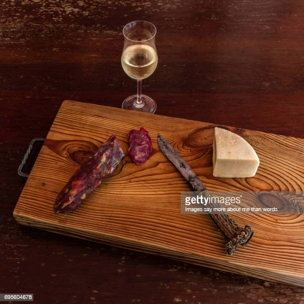 Board with cheese, salami, wine and old knife. Still life.