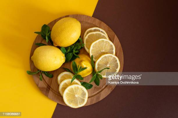 board with cut lemons and zest on wooden table, closeup - 酸っぱい ストックフォトと画像