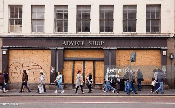 boarded up shop in a busy edinburgh street - boarded up stock photos and pictures