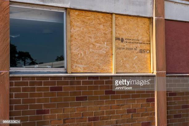 Boarded up smashed windows on a school building