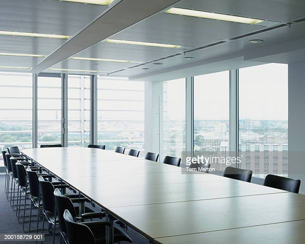 Boardroom table and chairs, by windows overlooking cityscape