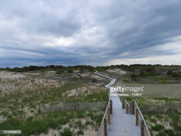 boardwalk amidst field against cloudy sky - greg nadeau stock pictures, royalty-free photos & images