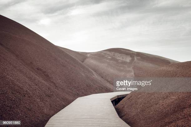 Boardwalk by painted hills against clear sky