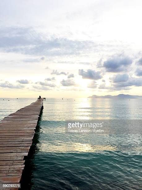 Boardwalk Jetty In Sea Against Sky