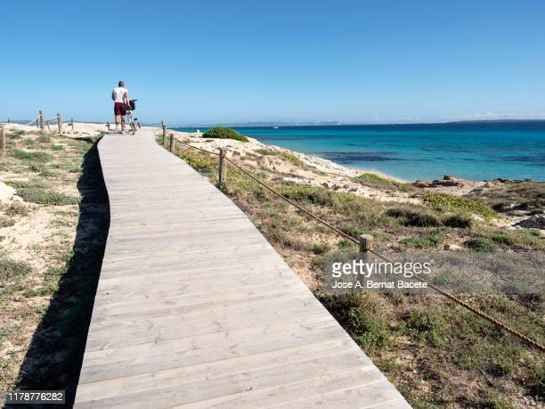 boardwalk leading towards beach against clear blue sky in formentera island, spain. - midday stock pictures, royalty-free photos & images