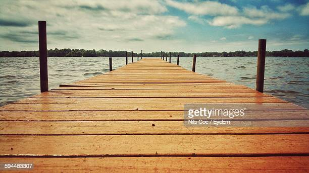 Boardwalk Leading Towards River Against Cloudy Sky
