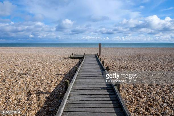 boardwalk leading towards sea against sky - dungeness stock pictures, royalty-free photos & images