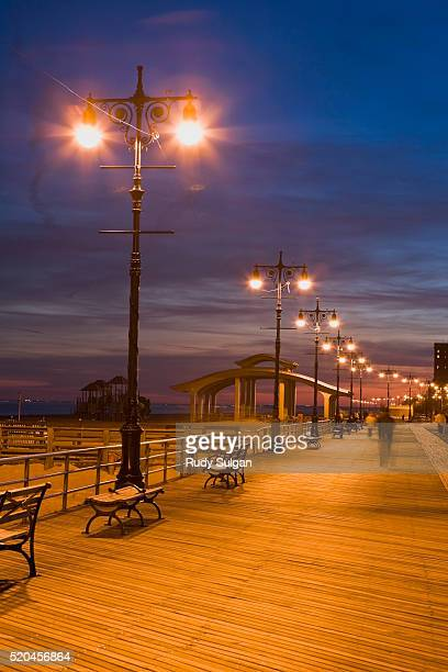 boardwalk on coney island at twilight - pavilion stock pictures, royalty-free photos & images