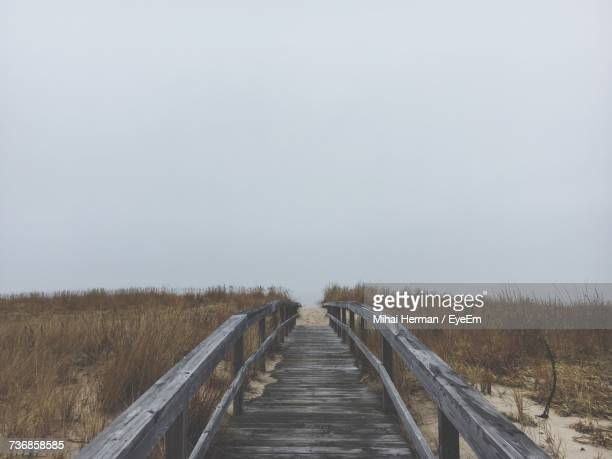 boardwalk on field against clear sky - bethany beach stock photos and pictures