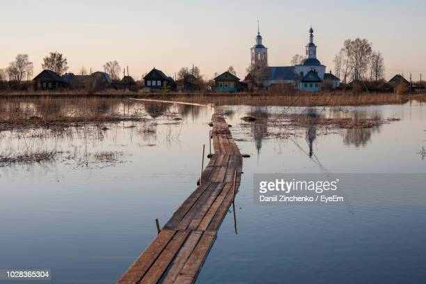 boardwalk on lake against sky - zinchenko stock pictures, royalty-free photos & images