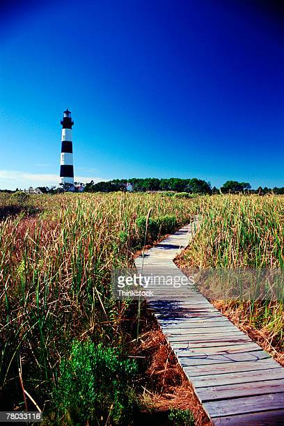 A boardwalk through marshes leads to the Bodie Island Light in the Outer Banks of North Carolina.