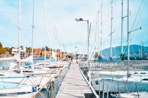 hobart, tasmania - april 02, 2012: boardwalk to sail boats at kangaroo bay, hobart. sailboats moored on the open water. - hobart tasmania stock pictures, royalty-free photos & images