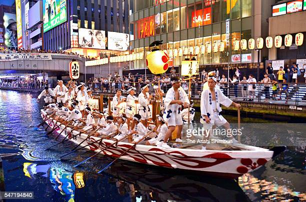 A boart carrying men wearing 'Happi' festival costumes cruises at Dotonbori River during the 'Funatogyo' river crossing ritual in pray for people's...