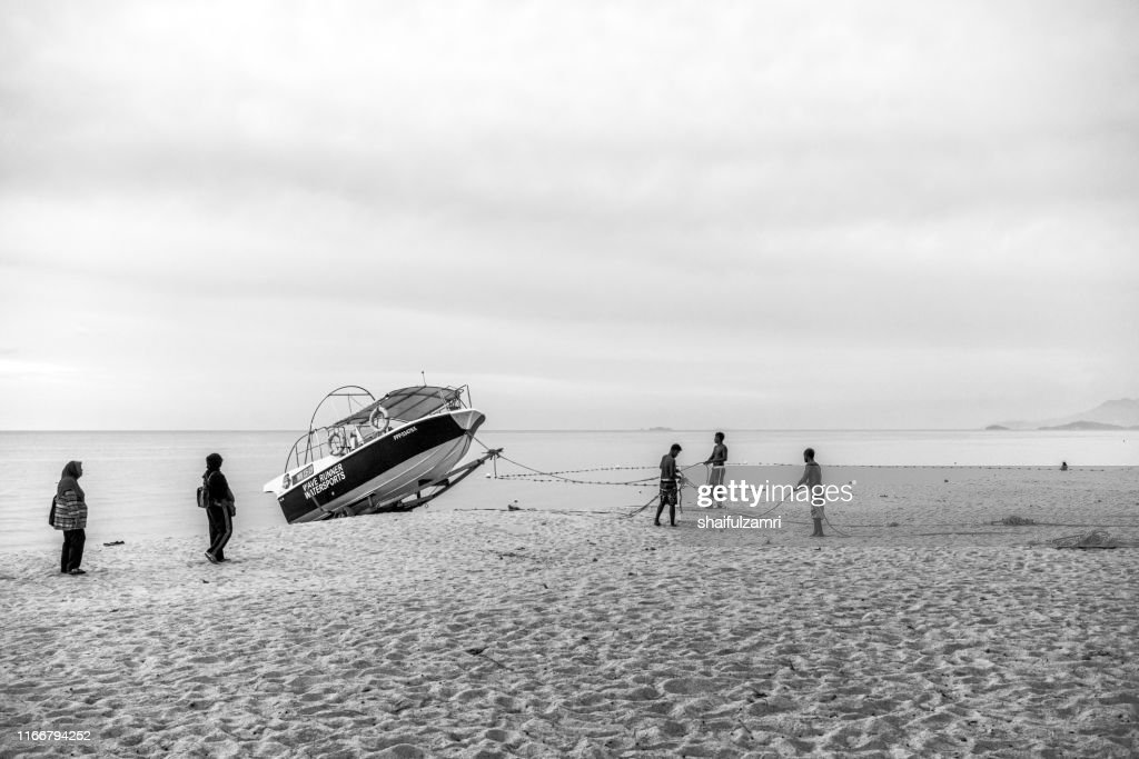 Boat activities over Batu Feringgi beach at Penang, Malaysia. Black and white. : Stock Photo