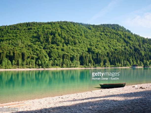 boat anchored on bank of alps lake. mountains mirrored in smooth water level of blue lake. - flussufer stock-fotos und bilder