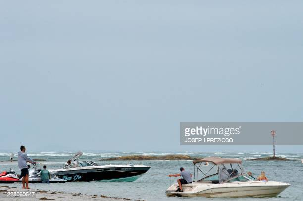 A boat anchors itself onto the shore at Wingaersheek Beach in Gloucester Massachusetts on August 15 2020 Over the past summer weekends hundreds of...