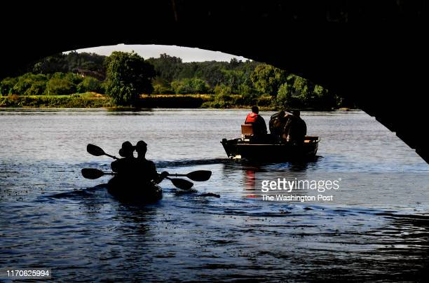 A boat and a double kayak head into the Potomac River at Riley's Lock on July 14 2019 The Chesapeake and Ohio Canal Towpath is above on top of the...