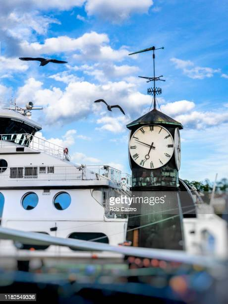 boat and clock by the harbor of oslo - rob castro stock pictures, royalty-free photos & images