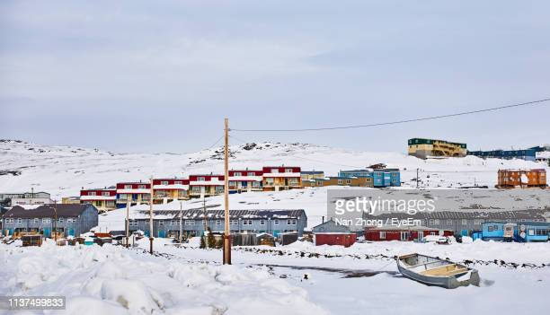 boat and houses on snow against sky - nunavut stock pictures, royalty-free photos & images