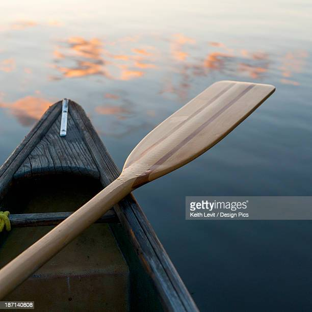 A Boat And Paddle Sit On A Tranquil Lake With Clouds Reflected In The Water