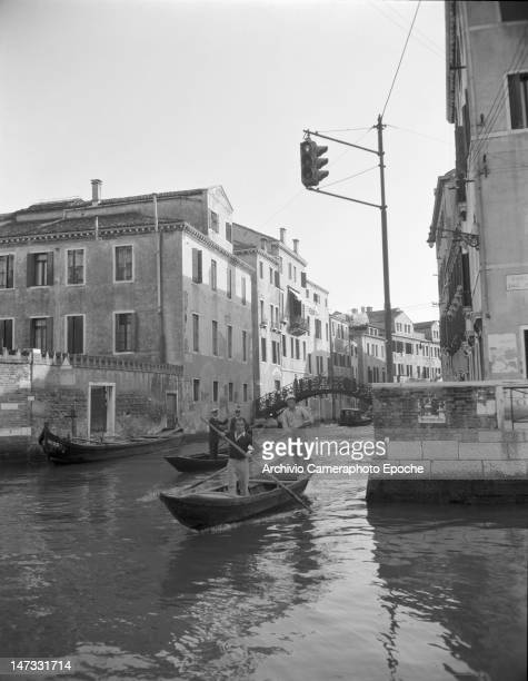 A boat and two gondolas crossing the canal and passing below the traffic light Venice 1951