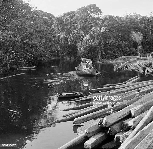 A boat approaches two Maroon women and child climb on lumber close to river shore near their village The Maroon Communities are comprised of escaped...
