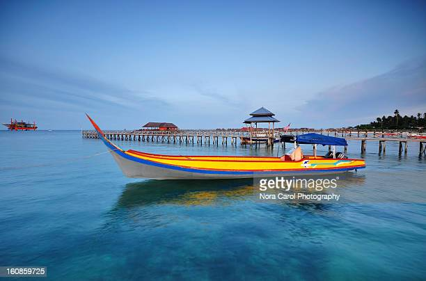 a boat at dusk with a long jetty as a backdrop - mabul island stock photos and pictures
