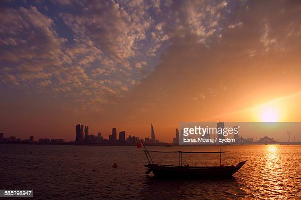 boat at lake against sky during sunset in city - bahrain stock pictures, royalty-free photos & images