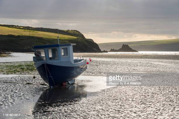 boat at low tide, newport sands, pembrokeshire, wales - low tide stock pictures, royalty-free photos & images