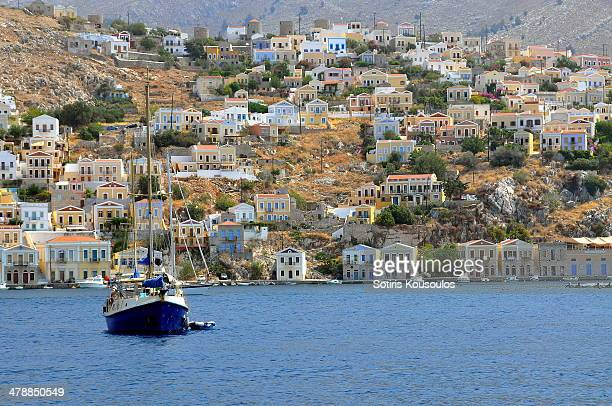 a boat at symi island port - symi stock photos and pictures