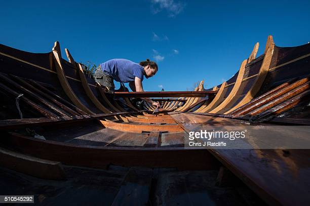 Boat builder Eddie Knight cleans out a Thames Skiff dating from 1890 after renovating it at the traditional Richmond Bridge Boathouses on the banks...